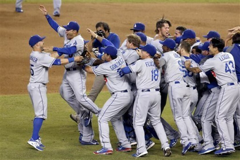 Los Angeles Dodgers players, including Skip Schumaker, left, and Jerry Hairston Jr., second from left, celebrate after winning the NL West title with a 7-6 win over the Arizona Diamondbacks in a baseball game Thursday, Sept. 19, 2013, in Phoenix. (AP Photo/Ross D. Franklin)