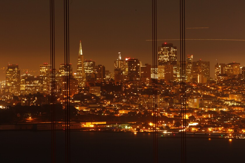 Framed by wires from the Golden Gate Bridge, the San Francisco skyline shimmers in the evening just after sunset. San Francisco is the most expensive destination for business travelers, a new study shows.