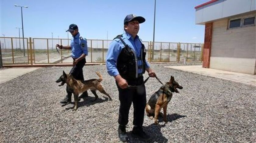 Iranian customs officers with drug-sniffing dogs at a customs house on the Afghanistan border in 2014.