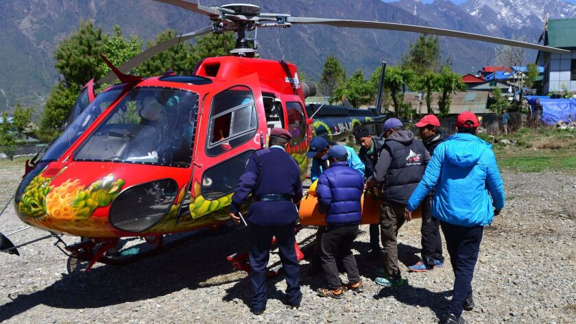Official carry the body of Nepalese mountaineer Min Bahadur Sherchan brought to Lukla heli pad on Ma