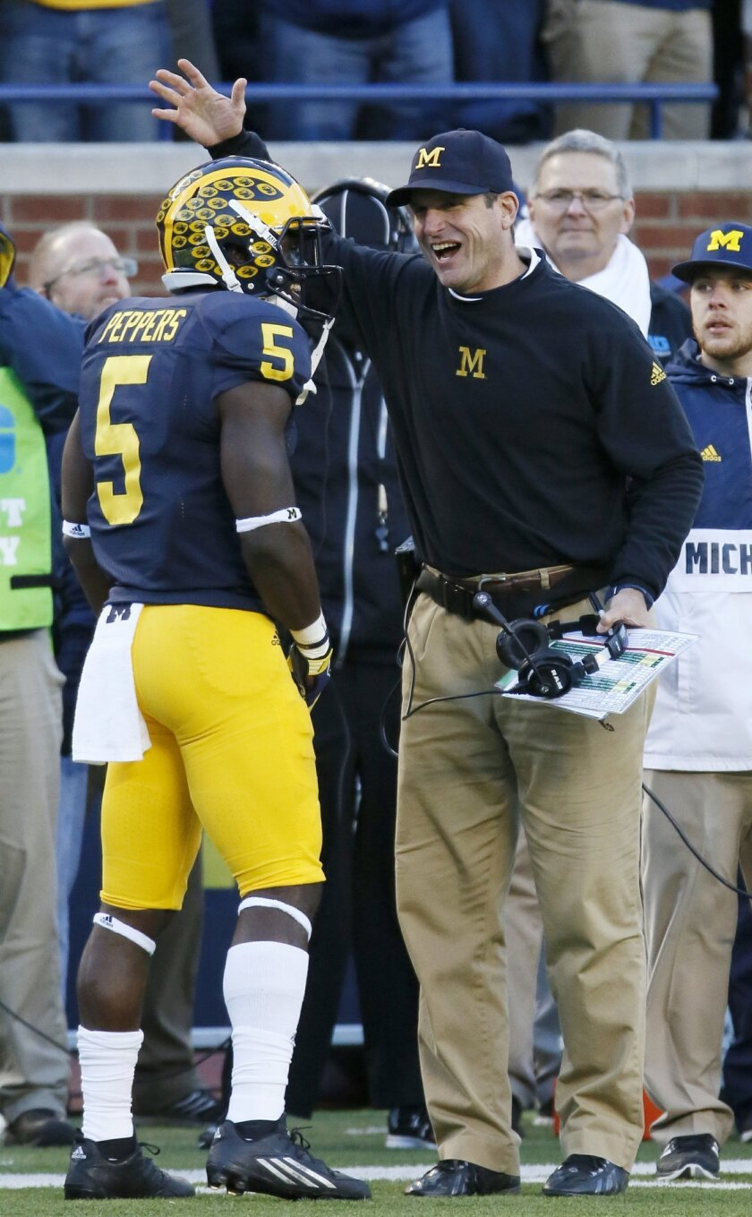 Michigan's Jabrill Peppers (5) celebrates with head coach Jim Harbaugh after scoring a touchdown against Rutgers during the first half of an NCAA college football game Saturday, Nov. 7, 2015, in Ann Arbor, Mich. (AP Photo/Duane Burleson)