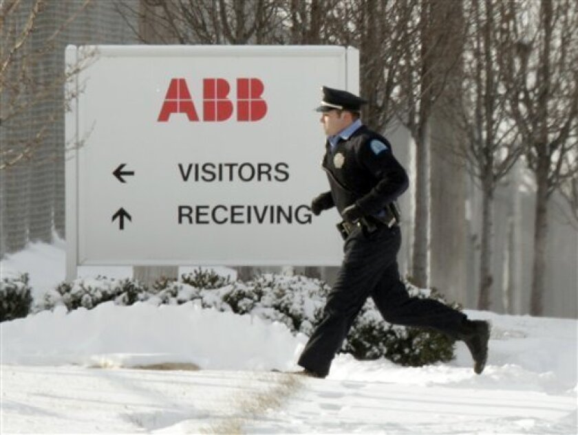 Police run into a building as they search for a gunman who walked into an ABB Power Plant, with an assault rifle and began shooting Thursday, Jan. 7, 2010, in St. Louis. (AP Photo/Jeff Roberson)