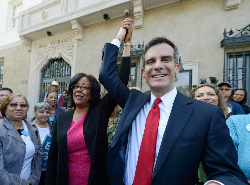 Mayoral candidate Eric Garcetti holds up the arm of one-time mayoral candidate Jan Perry after she threw her support behind him in the Los Angeles mayoral race.