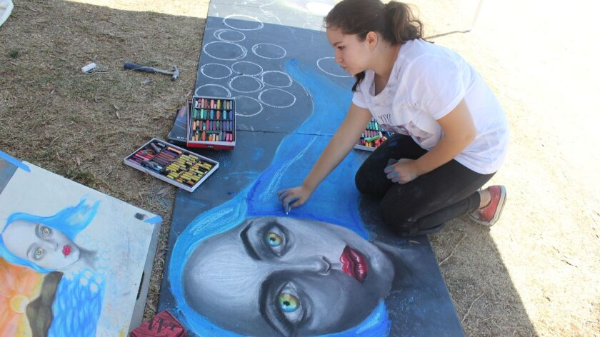 Lidia Vazquez working on a community mural at the August Harborfest in Chula Vista
