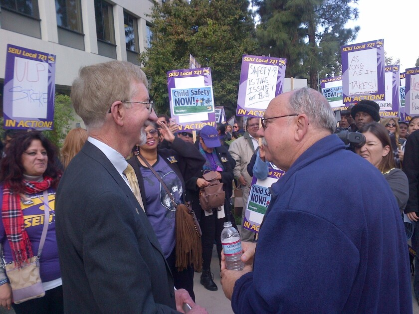 Los Angeles County child-welfare chief Philip Browning, left, appears at a rally for striking social workers. He asked that they return to work. At right is SEIU Local 721 President Bob Schoonover.