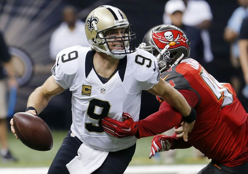FILE - In this Sept. 20, 2015 file photo, New Orleans Saints quarterback Drew Brees (9) scrambles under pressure from Tampa Bay Buccaneers defensive end George Johnson (94) in the first half of an NFL football game in New Orleans. The Saints have fallen to 0-2 because of a mistake-filled performance that drew boos from fans in the Superdome. Be it penalties, turnovers, blown assignments, special teams slip-ups or substitution problems, coach Sean Payton has a lot to address before a tough Week 3 contest at Carolina. (AP Photo/Bill Haber)