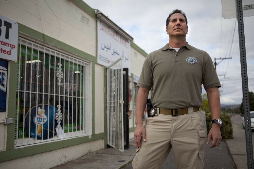 Sheriff's Lt. Marco Garmo stands before the El Cajon Market where 31 years ago on Christmas Eve he and his father were attacked and robbed. That event led Garmo, a Chaldean immigrant, to decide on a career in law enforcement rather than go into business like his father and other family members.