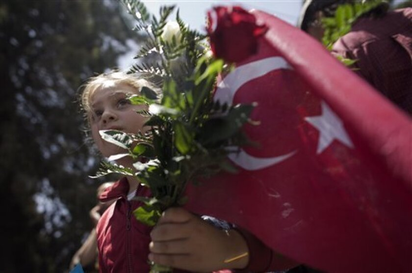 A Palestinian girl holds flowers with a Turkish flag near the Turkish consulate during a protest against the Israeli naval commando raid on a flotilla attempting to break the blockade on Gaza, in the east Jerusalem neighborhood of Sheikh Jarrah, Tuesday, June 1, 2010.  Some activists seized by Isra