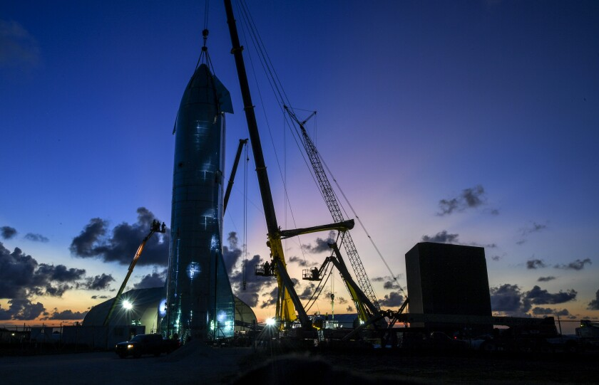 A crane operates near the top of a SpaceX Starship test rocket.