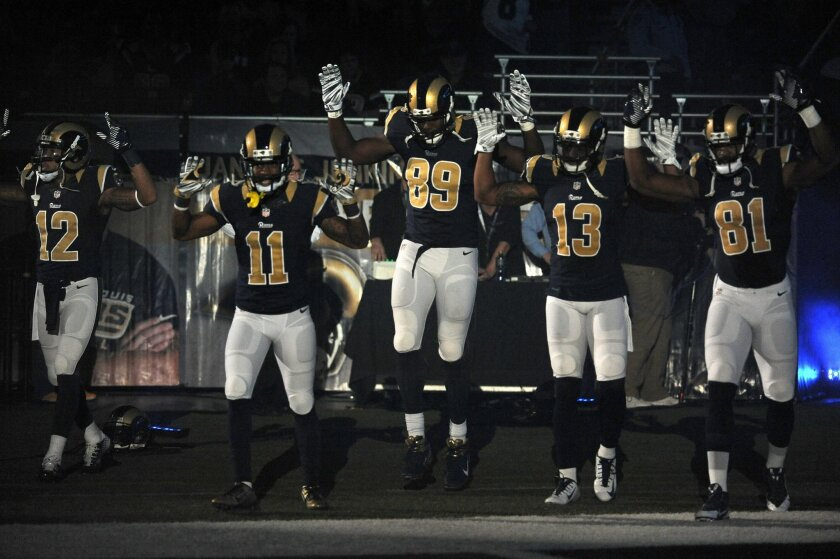 "ADDS SIGNIFICANCE OF THE RAISED ARMS -- Members of the St. Louis Rams raise their arms in awareness of the events in Ferguson, Mo., as they walk onto the field during introductions before an NFL football game against the Oakland Raiders, Sunday, Nov. 30, 2014, in St. Louis. The players said after the game, they raised their arms in a ""hands up"" gesture to acknowledge the events in Ferguson. (AP Photo/L.G. Patterson)"