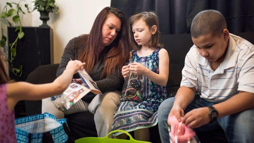 Rebecca Hendricks makes influenza awareness kits with her children Breanna Taylor, Audreana Taylor,
