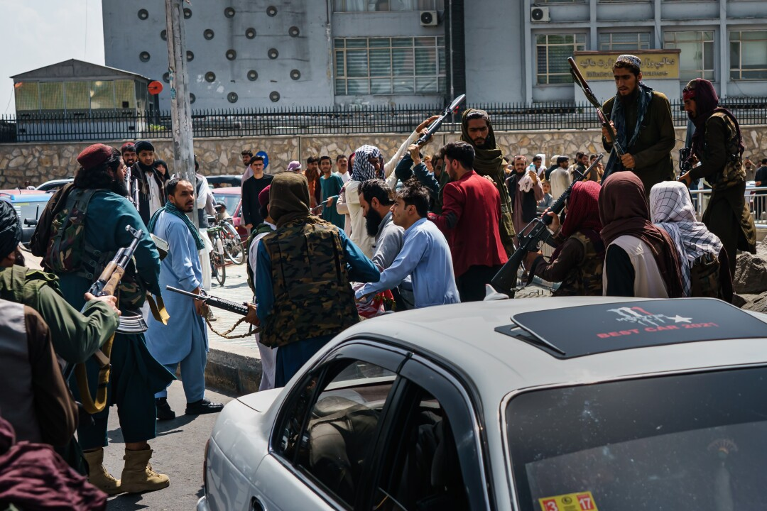 Taliban confront and push people as they try to control the crowd.