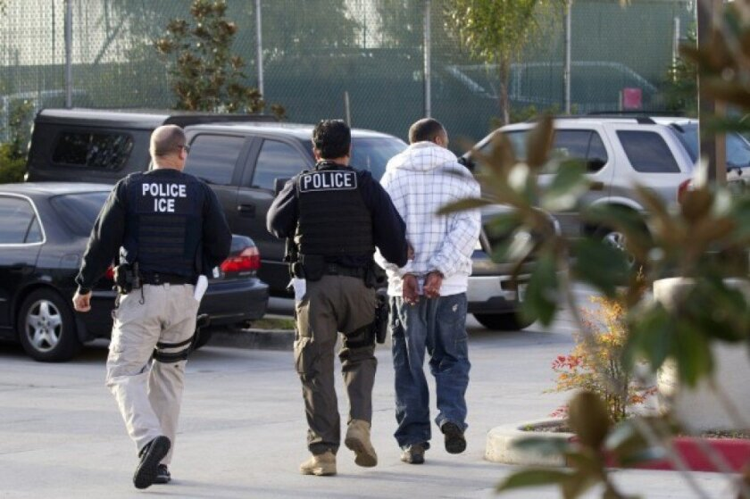 In this March 30, 2012 photo, Immigration and Customs Enforcement (ICE) agents take a suspect into custody as part of a nationwide immigration sweep in Chula Vista.