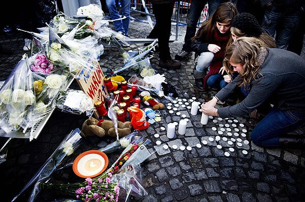 People light candles and place flowers as victims of the tragedy are remembered in Place Saint-Lambert, Liege, Belgium. A wounded child died late Tuesday after the shooting and grenade attack on a Belgian Christmas market, raising the death toll to five, a news report said, including the perpetrator.