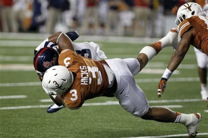 Texas linebacker Jordan Hicks (3) tackles Mississippi running back Jeff Scott (3) during the third quarter of an NCAA college football game Saturday, Sept. 14, 2013, in Austin, Texas. Ole Miss won 44-23. (AP Photo/Michael Thomas)