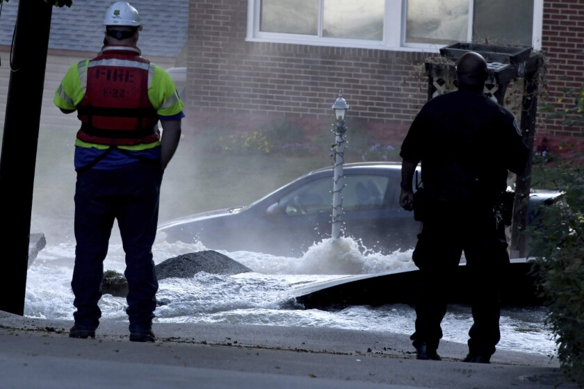 Water gushes from a 24-inch water main break on East Agnew Avenue. flooding homes, Friday, Sept. 20, 2019, in the Carrick section of Pittsburgh. (A massive water main break in Pittsburgh prompted the rescue of several people and pets, led to school closings and sent a torrent of water careening down streets, looking like river rapids.(Darrell Sapp/Pittsburgh Post-Gazette via AP)