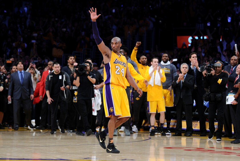 Kobe Bryant waves to the crowd as he walks off the court for the last time at Staples Center.