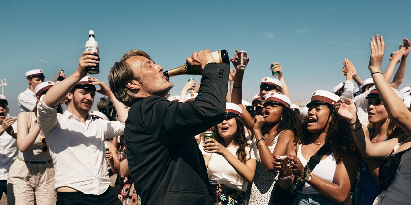 Mads Mikkelsen's character drinks from bottle in the midst of a crowd of celebrating students.