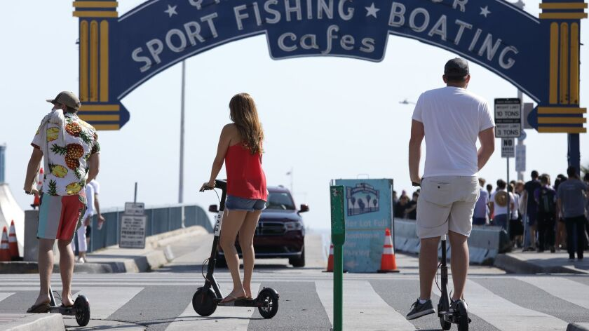 SANTA MONICA, CA-JUNE 06, 2018: A scooter rider rolls past the Santa Monica Pier. The Santa Monica C