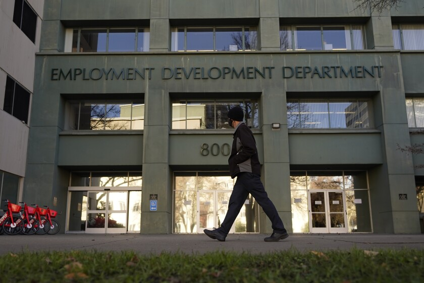 FILE - In this Dec. 18, 2020, file photo, a person passes the office of the California Employment Development Department in Sacramento, Calif. Some Americans are receiving tax forms saying they owe money on unemployment benefits they never received. The notices from state governments could be a sign of the extent of identity theft in the nation's state-run unemployment systems. Unemployment benefits are taxable, so government agencies must send a tax form to people who received them. (AP Photo/Rich Pedroncelli, File)