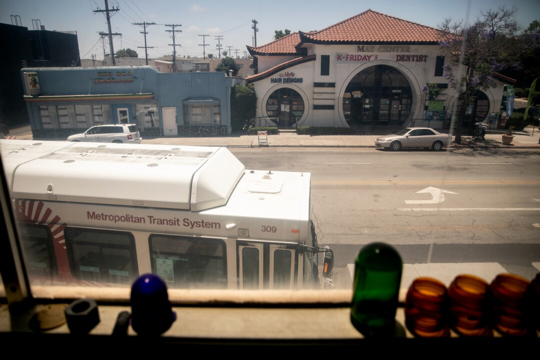 The number 7 bus passes by as seen from the upstairs at San Diego Electric store.
