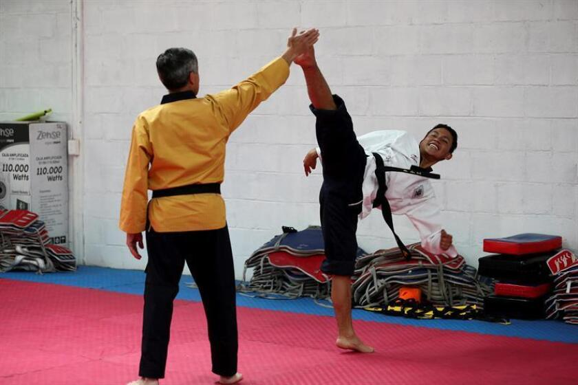Edison Joel Chiguano (d) patea durante un entrenamiento con su entrenador Marcelo Prado este lunes, en Quito (Ecuador). EFE