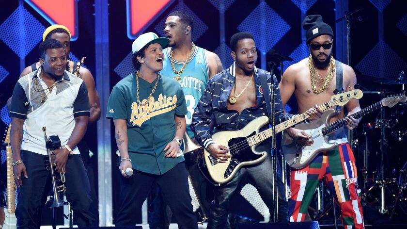 Bruno Mars, in an Oakland Athletics jersey, with members of his band.