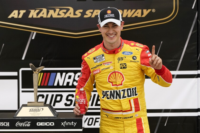 Joey Logano celebrates in victory lane after winning a NASCAR Cup Series auto race at Kansas Speedway.