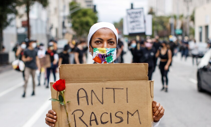 """Katyana DeCampos marches with a sign with the words """"Anti Racism"""" during a protest in Los Angeles in June."""