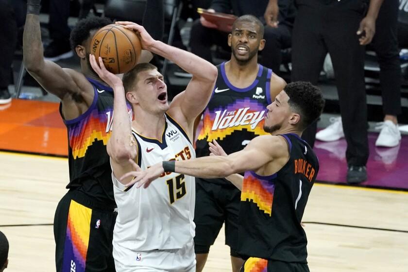 Denver Nuggets center Nikola Jokic (15) shoots over Phoenix Suns guard Devin Booker (1) during Game 1 of an NBA basketball second-round playoff series, Monday, June 7, 2021, in Phoenix. (AP Photo/Matt York)