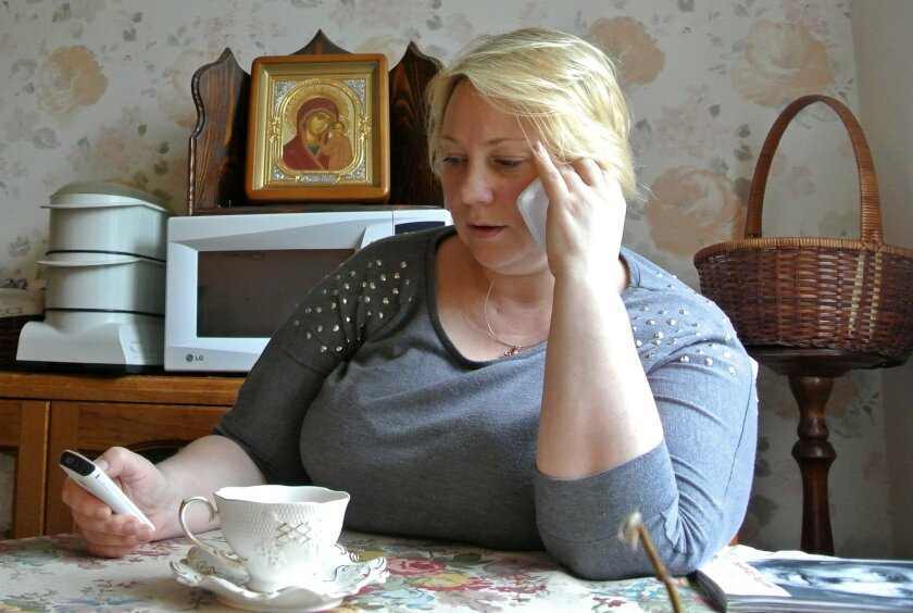 In this Friday, Sept. 4, 2015 photo Alla Kravtsova speaks on a phone at her home in northern Moscow. Kravtsova's husband, a former intelligence employee Gennady Kravtsov, is on trial on treason charges for sending a cover letter to Sweden. The Russian government increasingly has portrayed any cooperation with foreign companies or nationals as a potential security threat, a throwback to Soviet times when any contact with foreigners aroused suspicion. (AP Photo/Nataliya Vasilyeva)