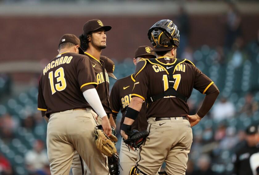 Teammates surround Padres pitcher Yu Darvish on the mound