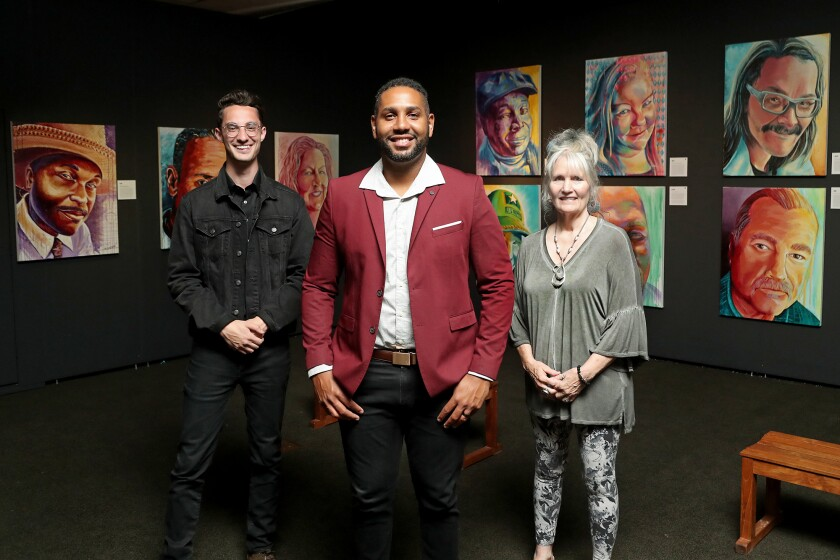 Artists pose for a portrait in front of a display of paintings in a gallery