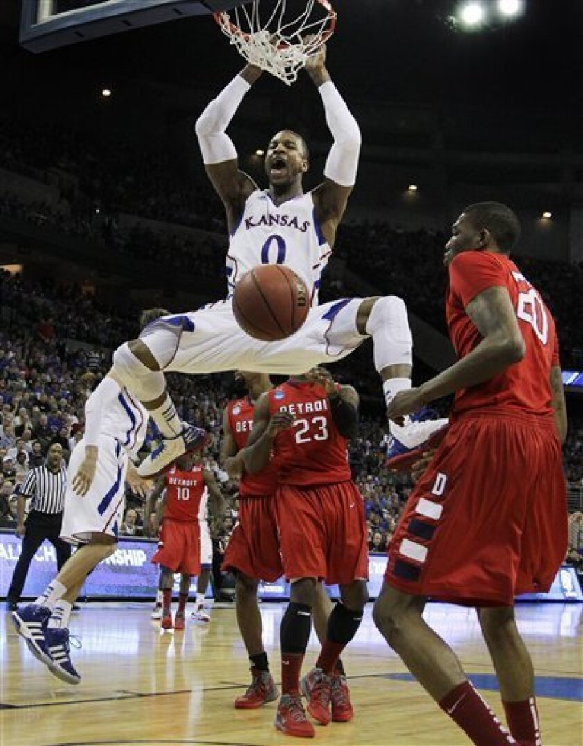 Kansas forward Thomas Robinson (0) dunks next to Detroit center LaMarcus Lowe (20) during the first half of an NCAA college basketball tournament game at CenturyLink Center in Omaha, Neb., Friday, March 16, 2012. (AP Photo/Nati Harnik)
