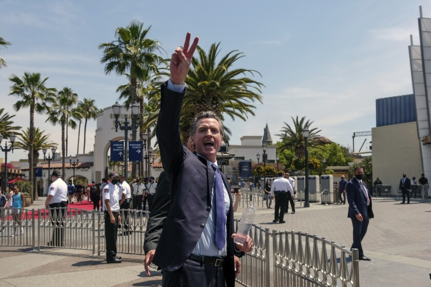 FILE - In this June 15, 2021 file photo California Governor Gavin Newsom gestures after a news conference at Universal Studios in Universal City, Calif. On Thursday, June 17, 2021, Newsom released his first ads in the recall campaign against him, with one highlighting recent positive news including cash payments to Californians. (AP Photo/Ringo H.W. Chiu, File)