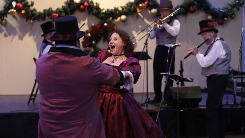 Mrs. and Mr. Fezziwig dance to polka music inside Dickens Village during Winter Fest OC at the OC Fa