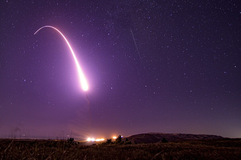 The glowing arc of a test missile launch against a starry night sky