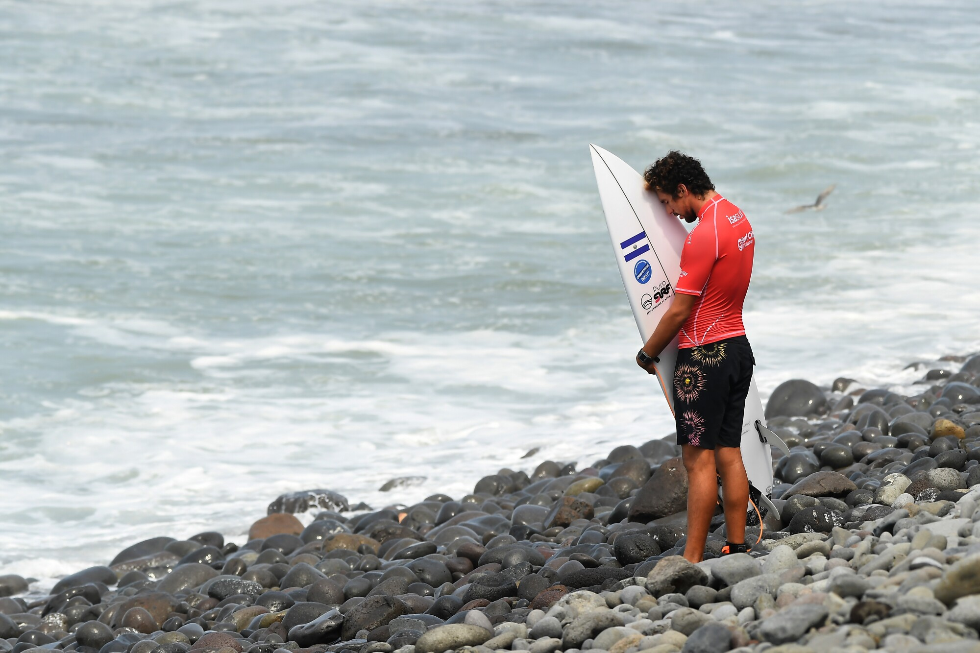 Surfer Bryan Perez prays before competing in the ISA World Surfing Games in El Salvador.