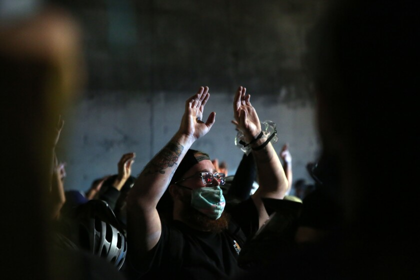 Demonstrators in downtown L.A. hold their hands up as police gather during a protest over the shooting of Jacob Blake.