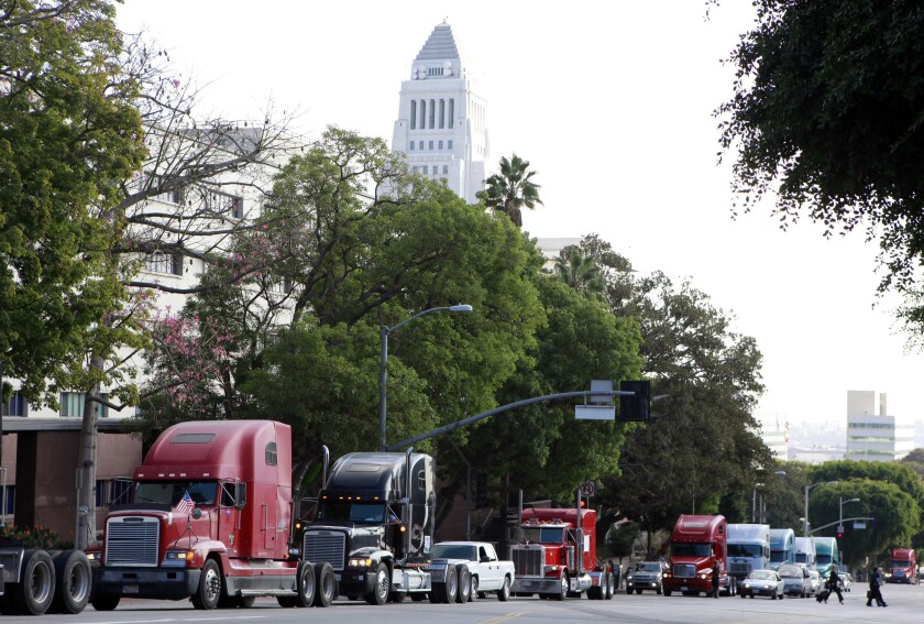 FILE - In this Friday, Nov. 13, 2009 file photo a caravan of trucks from the ports of Los Angeles and Long Beach, Calif., drive around Los Angeles City Hall during a protest against container fees being assessed against independent truckers. The California Trucking Association has filed what appears to be the first lawsuit challenging a sweeping new labor law that seeks to give wage and benefit protections to workers in the so-called gig economy, including rideshare drivers at companies such as Uber and Lyft. The federal lawsuit filed Tuesday, Nov. 12, 2019, contends that the legislation violates federal law and would deprive more than 70,000 independent truckers' of their ability to work. (AP Photo/Damian Dovarganes, File)