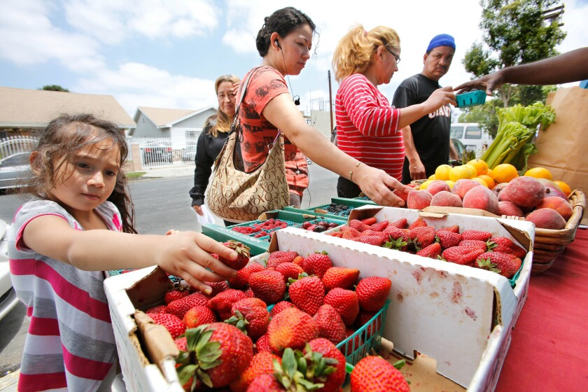Shoppers look at fruit on display at a produce stand set up outside St. John's Well Child and Family Center's S. Mark Taper Foundation Health Center in South Los Angeles in June 2013.
