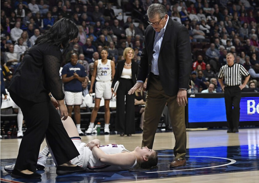 Athletic trainer Janelle Francisco, left, tends to injured player Kyla Irwin as Connecticut head coach Geno Auriemma talks with her during the second half of an NCAA college basketball game in the American Athletic Conference tournament semifinals against South Florida at Mohegan Sun Arena, Sunday, March 8, 2020, in Uncasville, Conn. (AP Photo/Jessica Hill)