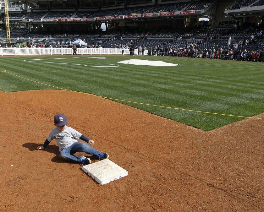 Padres fan Captain Burnett, 7, slides into third base at Petco Park's Padres Fan Fest Saturday.