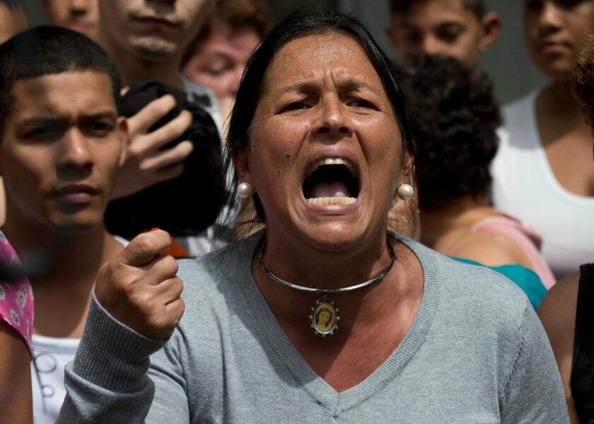 """A woman shouts """"Recall!"""" during a protest demanding food, a few blocks from Miraflores presidential palace in Caracas, Venezuela, Thursday, June 2, 2016. The opposition is demanding President Nicolas Maduro face a recall referendum this year amid rising frustration with widespread food shortages an"""