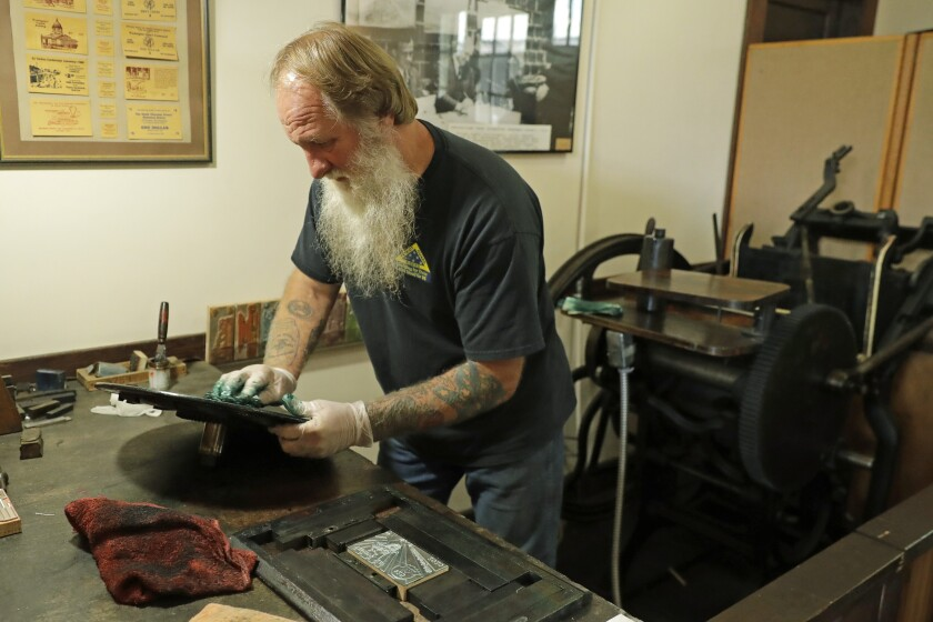 In this May 21, 2020 photo, Loren Ackerman cleans the ink plate of the 1890s-era press he uses to print wooden money in Tenino, Wash. In an effort to help residents and local merchants alike get through the economic fallout of the coronavirus pandemic, the small town has issued wooden currency for residents to spend at local businesses, decades after it created a similar program during the Great Depression. (AP Photo/Ted S. Warren)