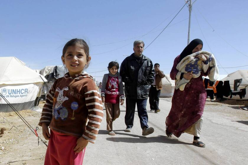 A Syrian family makes its way at the Zaatari refugee camp in Jordan. Initially created to shelter 50,000 refugees, the tent city is now home to about 108,000.