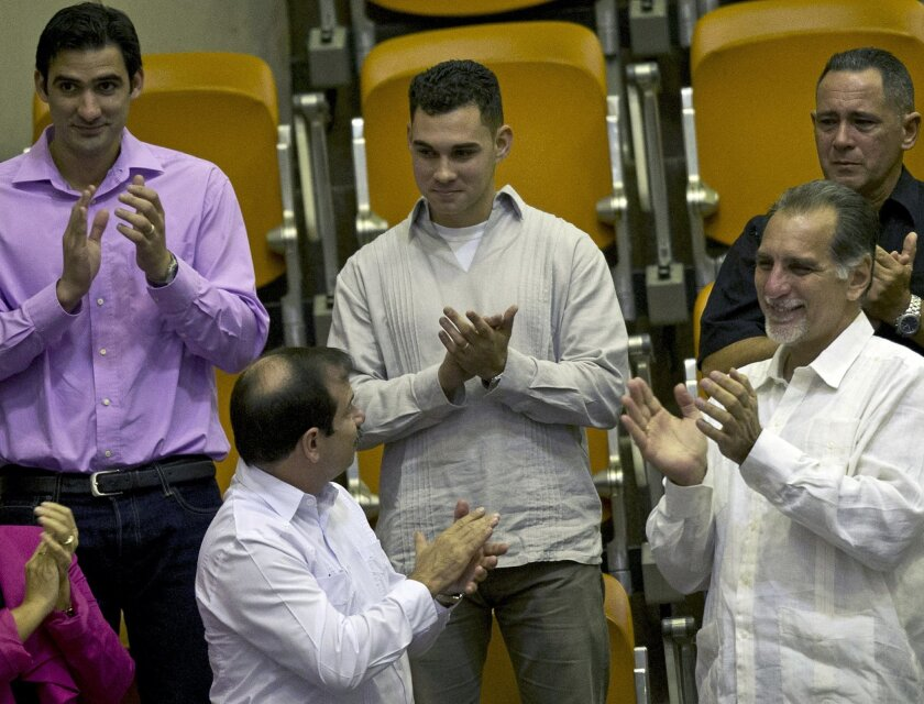"""FILE - In this Dec. 20, 2014 file photo, Elian Gonzalez, center, the young Cuban rafter who was at the center of a bitter custody battle in 2000 between relatives in Miami and his father in Cuba, is recognized with applause during the legislative session at the National Assembly in Havana, Cuba. Cuban government website Cubadebate reported Friday, July 15, 2016, the now 22-year-old Gonzalez received his diploma in industrial engineering from the University of Matanzas. Flanked by Fernando Gonzalez, bottom left, and Rene Gonzalez, front right, members of the """"Cuban Five"""" spy ring. (AP Photo/Ramon Espinosa)"""