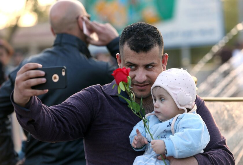 In this Saturday, Feb. 13, 2016 photo, an Iraqi man takes a photo with his child ahead of Valentine's Day at Zawra Park in Baghdad, Iraq. Baghdad is plastered with Valentine hearts and roses, and Iraqis are enjoying a rare lull in violence but wondering how long it will last. Despite recent setback