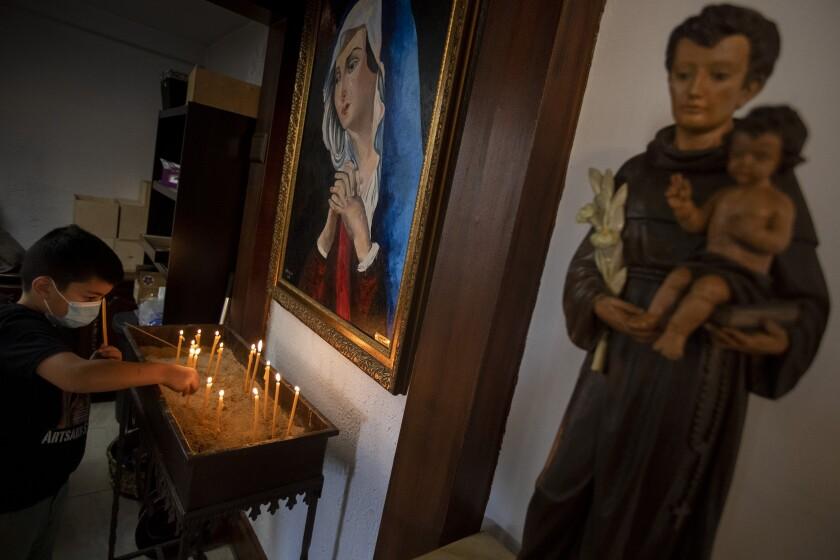 A boy lights a candle at an altar