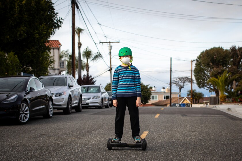 Children wearing face masks play in the streets of Redondo Beach, California during the coronavirus pandemic